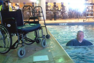 Dennis walking in water, abandoned wheelchair beside him.