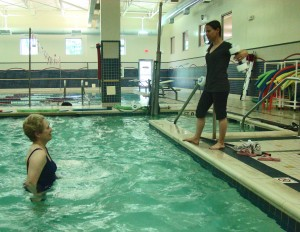 Janice follows Instructor Jennifer during Aquatic Pilates class.