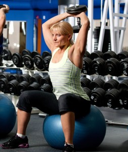 Engage multiple muscle groups with free weights. Extra points for balancing on fitness ball!