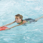 Middle aged woman in swimming pool with kickboard