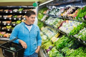 Hispanic man shopping for healthy food in supermarket